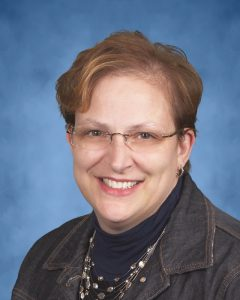 Photo of woman with short brown hair and glasses, smiling