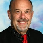 Smiling man with red tie and beard