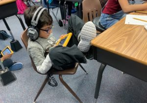 child with headphones using a tablet