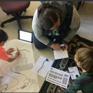 teacher working with students on ozobot project