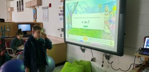 student presenting at an interactive whiteboard